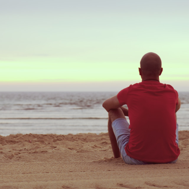 """""""Young man sitting in the beach sand at sunset"""" stock image"""