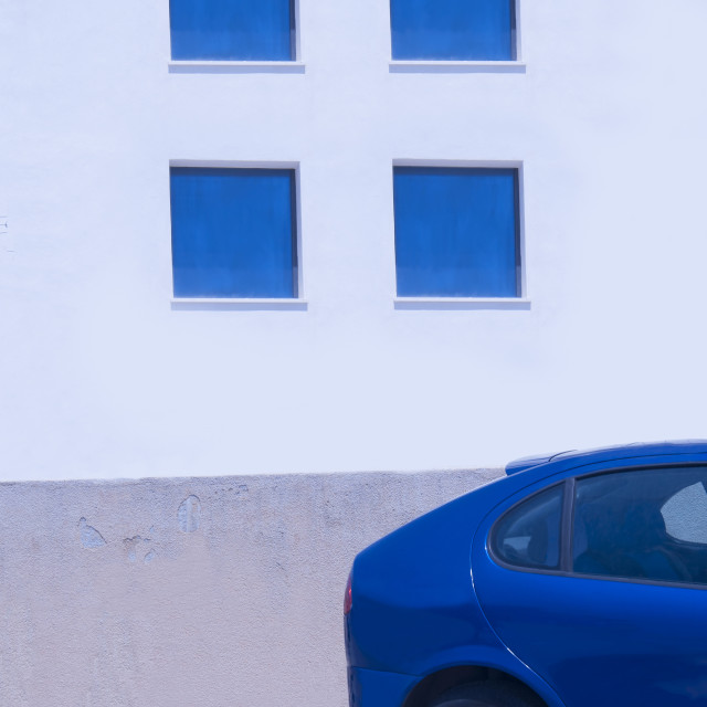 """Four blue windows on sunlit white wall and rear of blue abstract"" stock image"