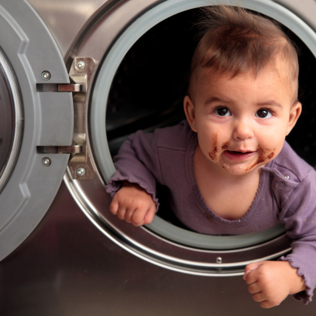 """""""dirty baby on a washer"""" stock image"""