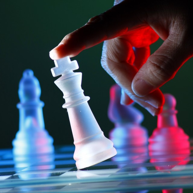 """Finger tilting a chess piece on Chess Board"" stock image"