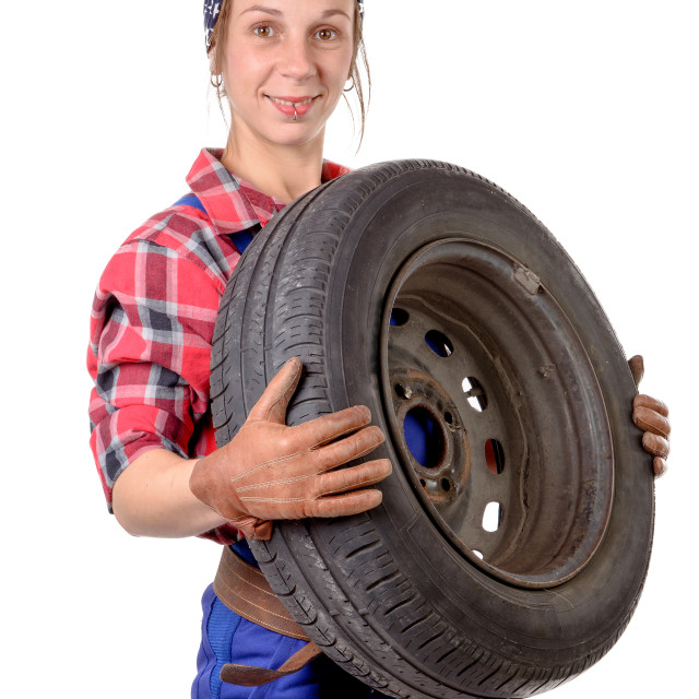 """young woman mechanic with a car wheel"" stock image"