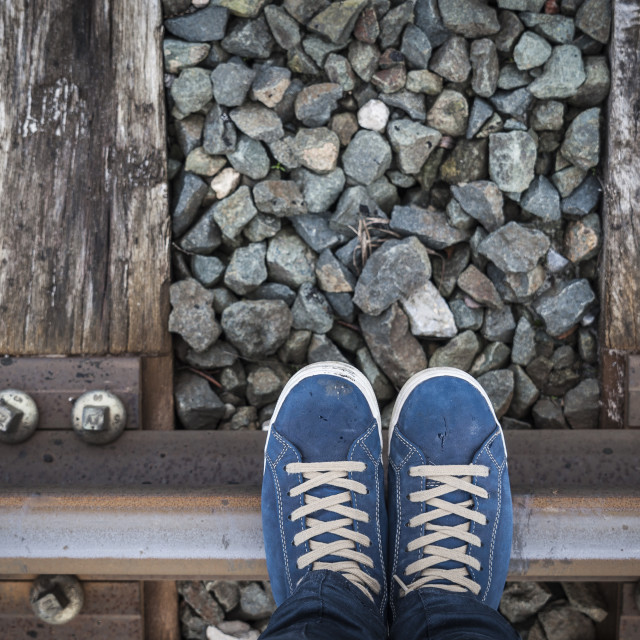 """Feet on urban shoes on a train railway"" stock image"