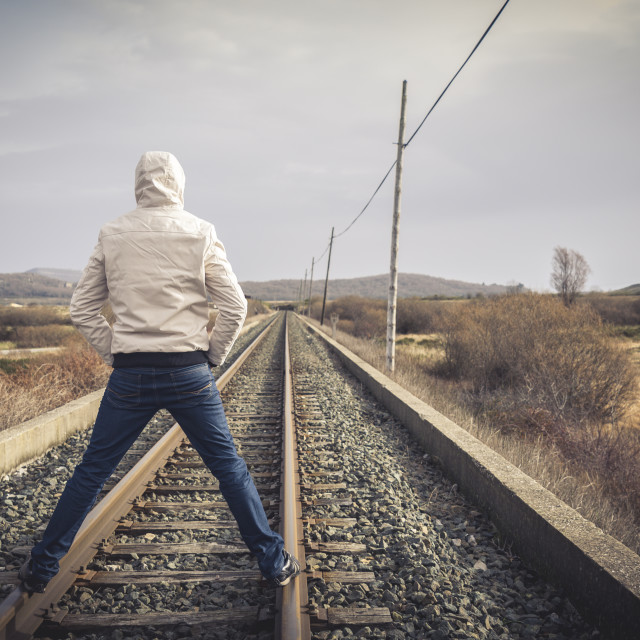 """Young man standing on a railway. Rural setting"" stock image"