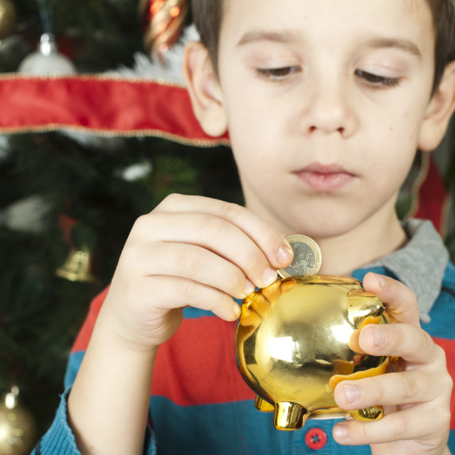 """""""Little boy puts a coin in cash pig"""" stock image"""