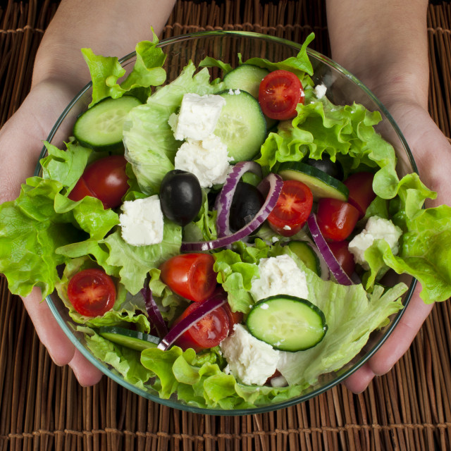 """Hands holding salad in a glass bowl"" stock image"