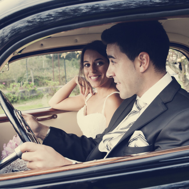 """Bride and groom inside a classic car, vintage tone"" stock image"