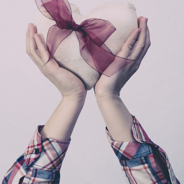 """Hands holding a white fabric heart with a red ribbon"" stock image"