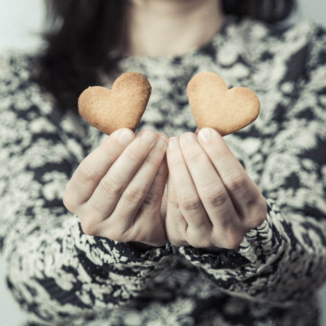 """Woman holding two heart shaped butter biscuit. Valentine's day"" stock image"