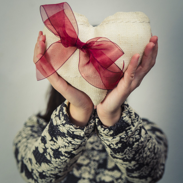 """Woman hiding his face with a fabric heart with a red ribbon. Valentine's day"" stock image"
