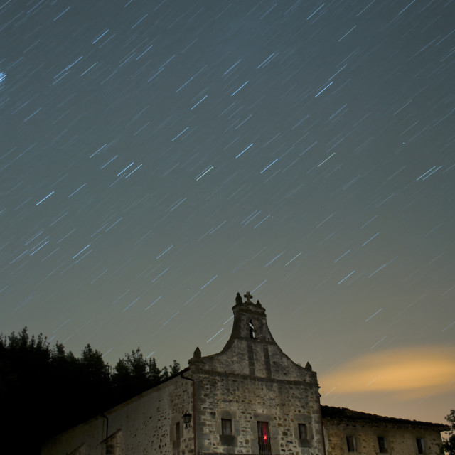 """""""Star trails in the sky over a rural church. Long exposure"""" stock image"""