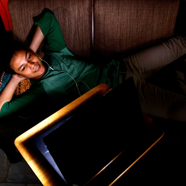"""Asian teen watching video on a laptop"" stock image"