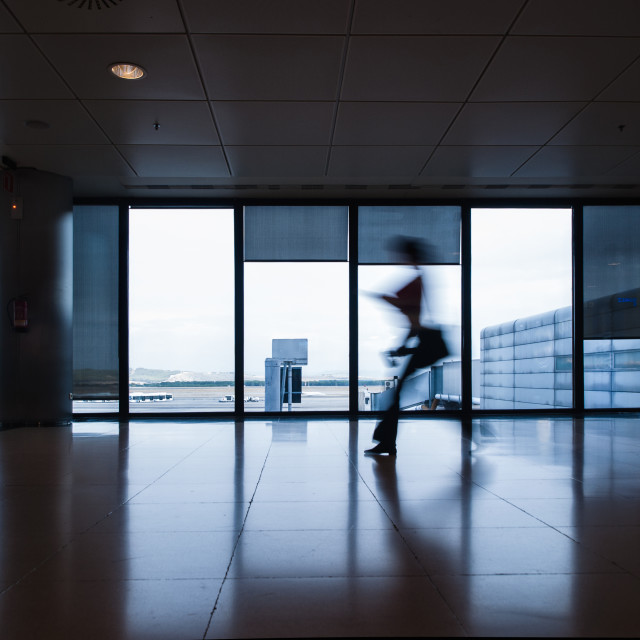 """""""Person in motion in an airport"""" stock image"""