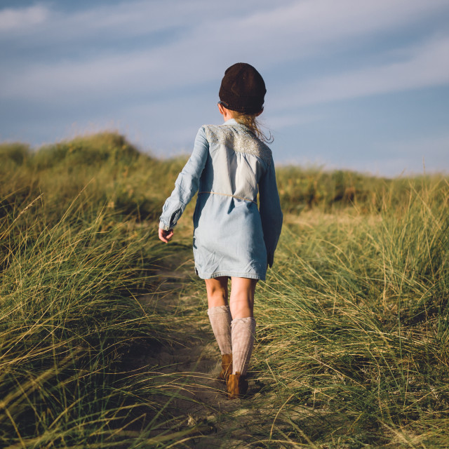 """""""Young girl walking on a trail to the beach."""" stock image"""