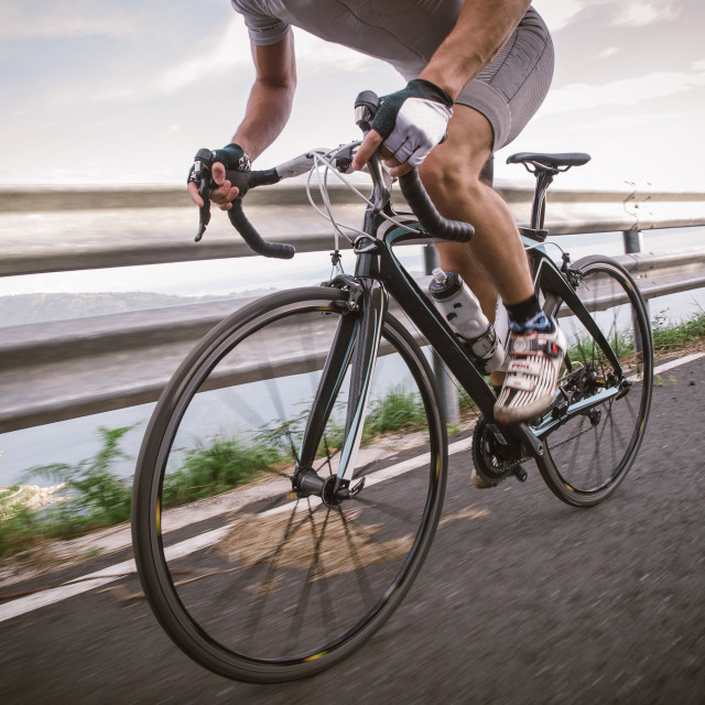 """Detail of a road bike with a cyclist pedaling"" stock image"
