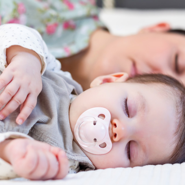 """Young mother and her baby girl sleeping in the bed"" stock image"