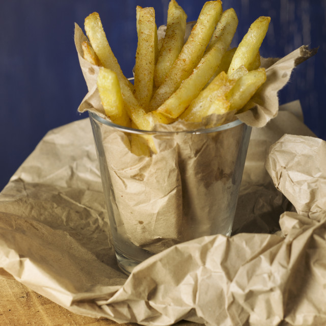 """french fries in a paper wrapper, blue background"" stock image"