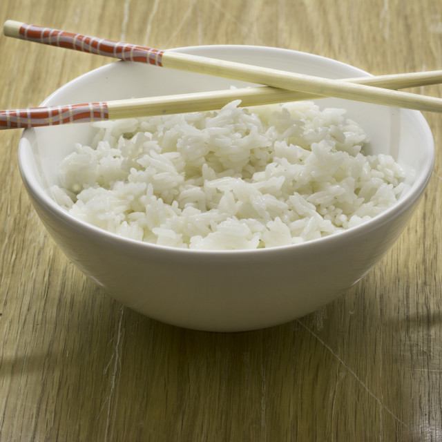 """Bowl of white rice with chopsticks, wooden background"" stock image"