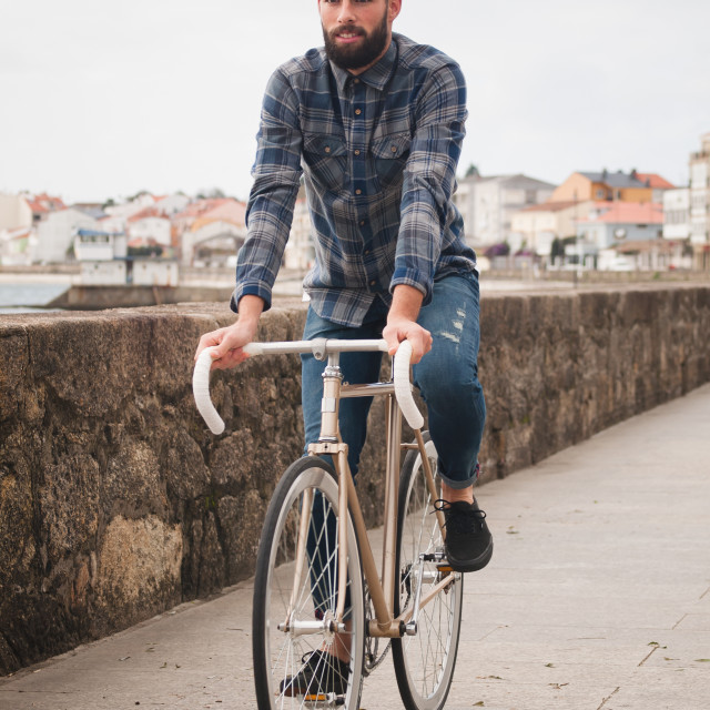 """Hipster man riding in a fixie bike"" stock image"