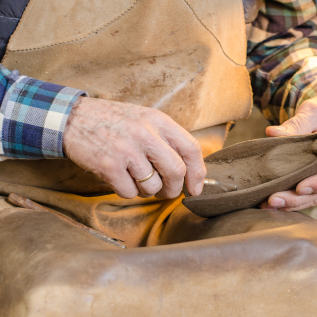 """Hands of a potter creating a clay figure"" stock image"