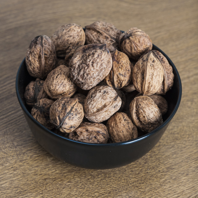 """Walnuts in a bowl on wooden table"" stock image"