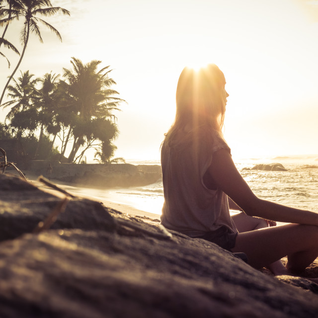 """A woman meditates on a tropical beach"" stock image"