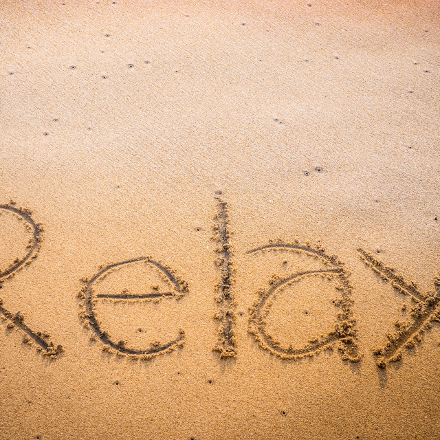 """""""Relax written into the sand on a beach"""" stock image"""