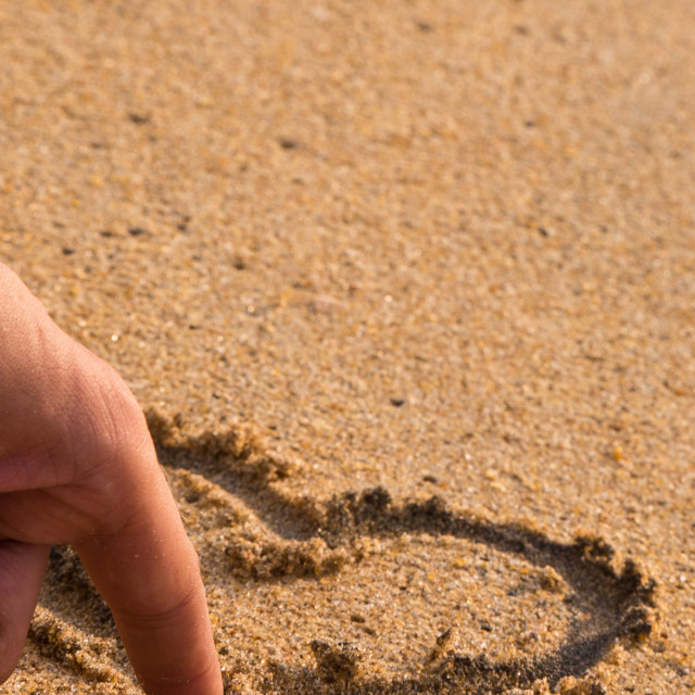 """""""FInger draws a love heart in the sand"""" stock image"""