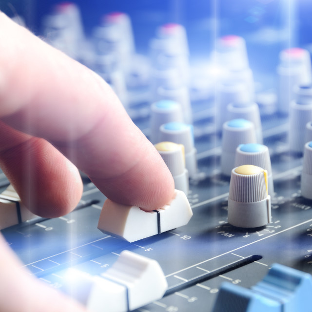 """Man adjusting audio mixer with flare"" stock image"