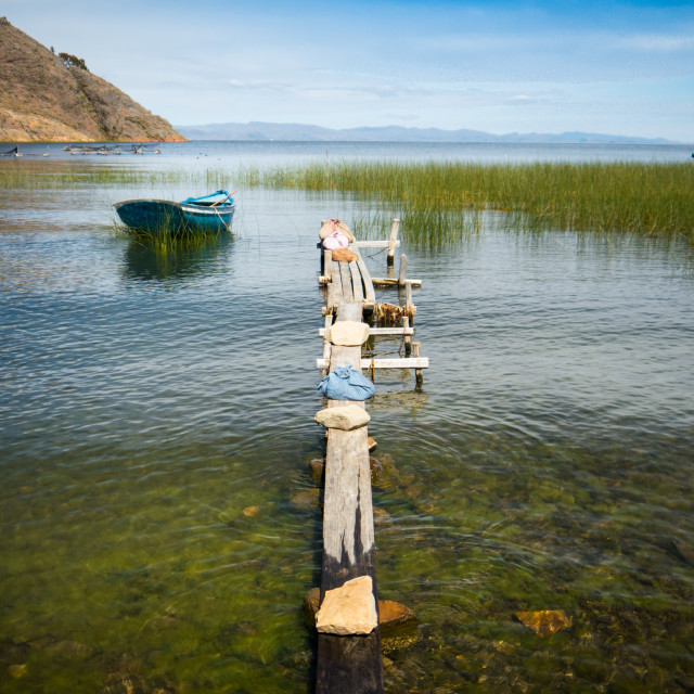 """A row boat sits peacefully on Lake Titicaca"" stock image"