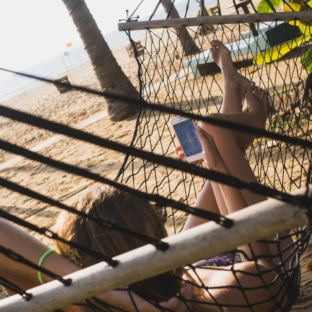 """Woman reading iphone on beach"" stock image"