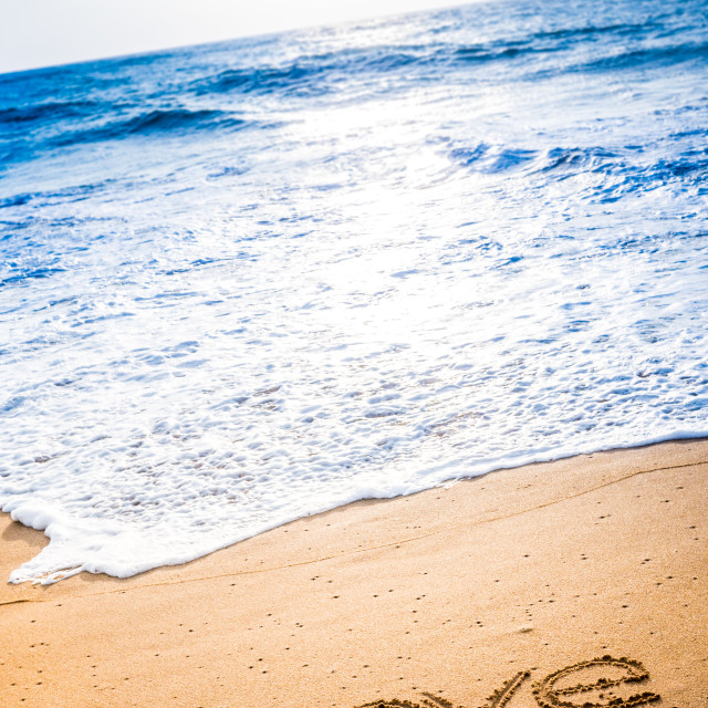 """The word LOVE written in the sand"" stock image"