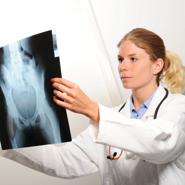 """""""Female doctor examining an x-ray image"""" stock image"""
