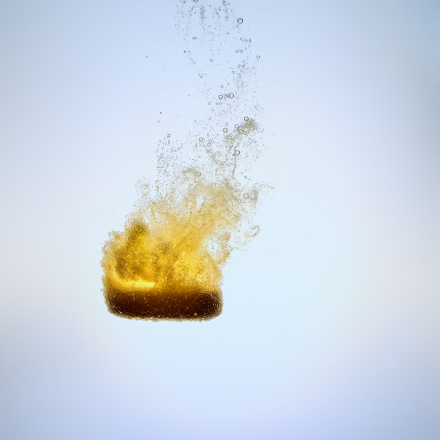 """effervescent orange tablet falling blue isolated"" stock image"