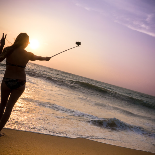 """Surfer chick takes selfie on beach at sunset"" stock image"