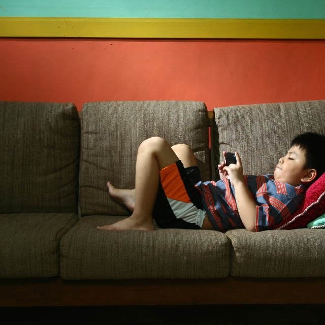 """""""Young kid using a tablet or smartphone on a couch"""" stock image"""