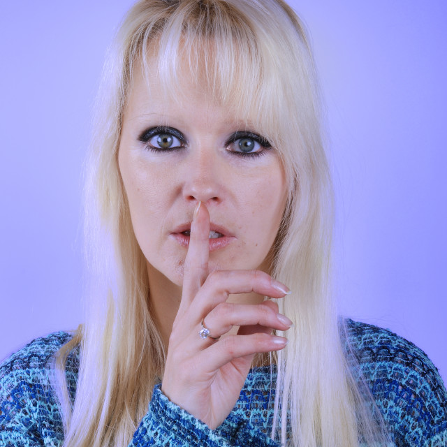 """""""Young blond woman making silence finger over her mouth"""" stock image"""