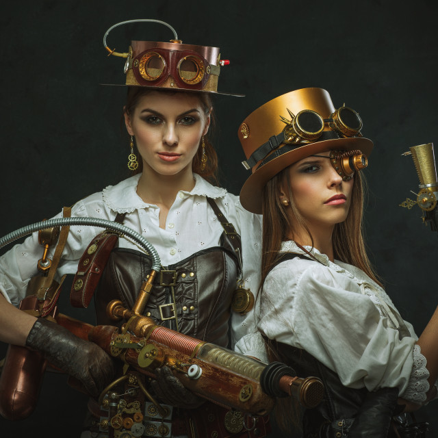 """Two girls dressed in the style of steampunk with arms"" stock image"