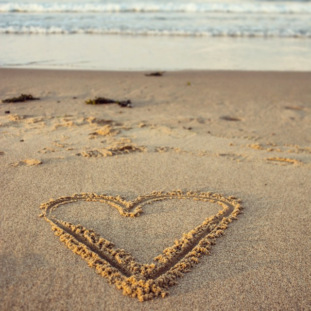"""Heart shape drawn in sand on the beach"" stock image"