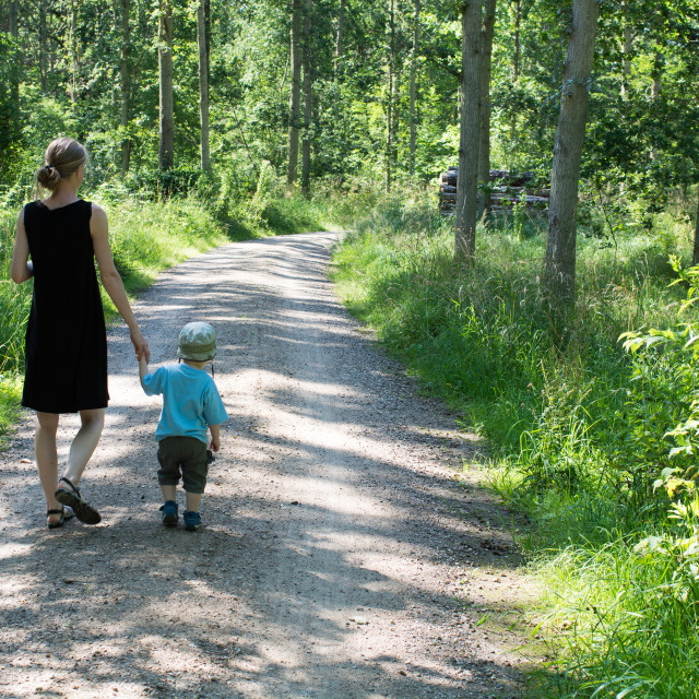 """Mother and child walking in a forest"" stock image"