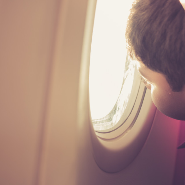 """Child Looks Out Airplane Window"" stock image"