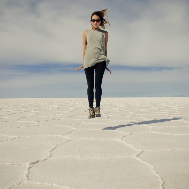 """Woman Jumps On Salt Flats of Bolivia"" stock image"