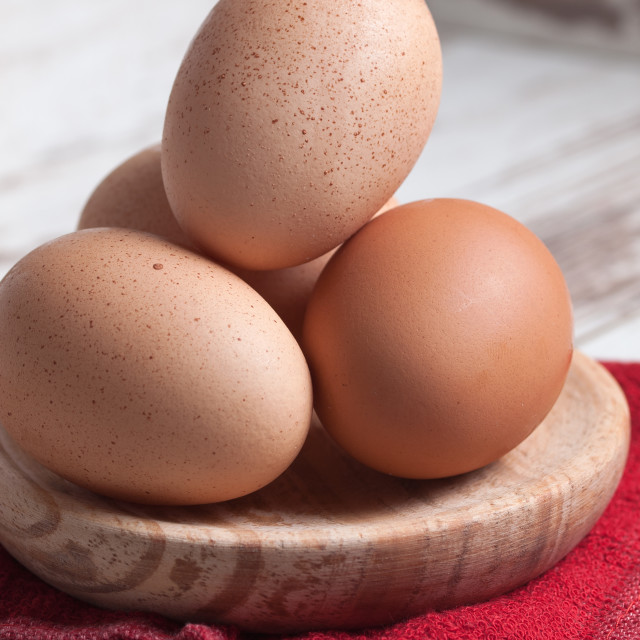 """""""Eggs piled on a wooden plate"""" stock image"""