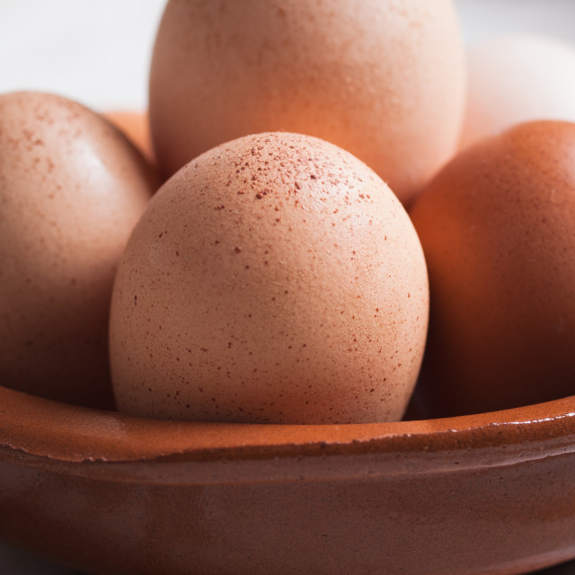 """""""Detail of eggs inside a clay plate over wooden background"""" stock image"""
