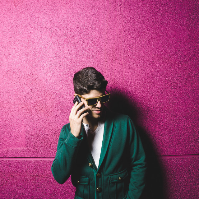 """""""Model man talking with a smart phone over fuchsia background"""" stock image"""