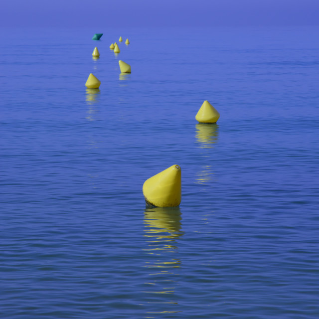 """Yellow buoys with reflections on deep blue water"" stock image"