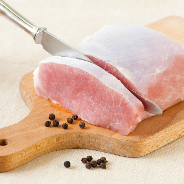 """Knife in pork meat for cutlets or schabowy"" stock image"