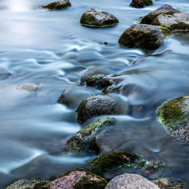 """Rocks in slow rinnig stream"" stock image"