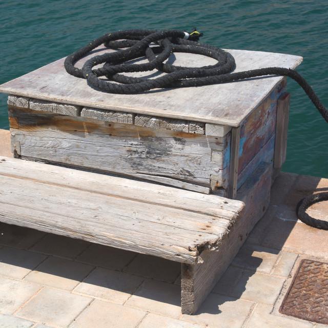 """Black mooring rope on wood box"" stock image"