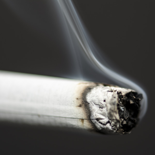"""Cigarette with smoke on black background"" stock image"