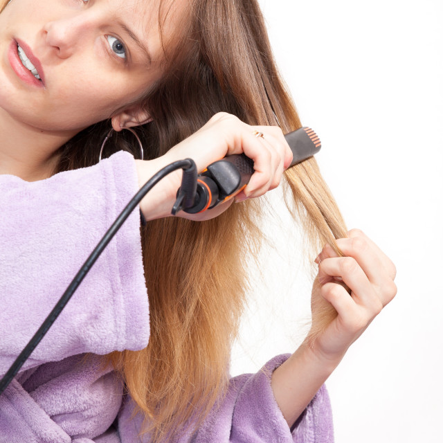 """""""pretty young woman straightening her hair with white background"""" stock image"""
